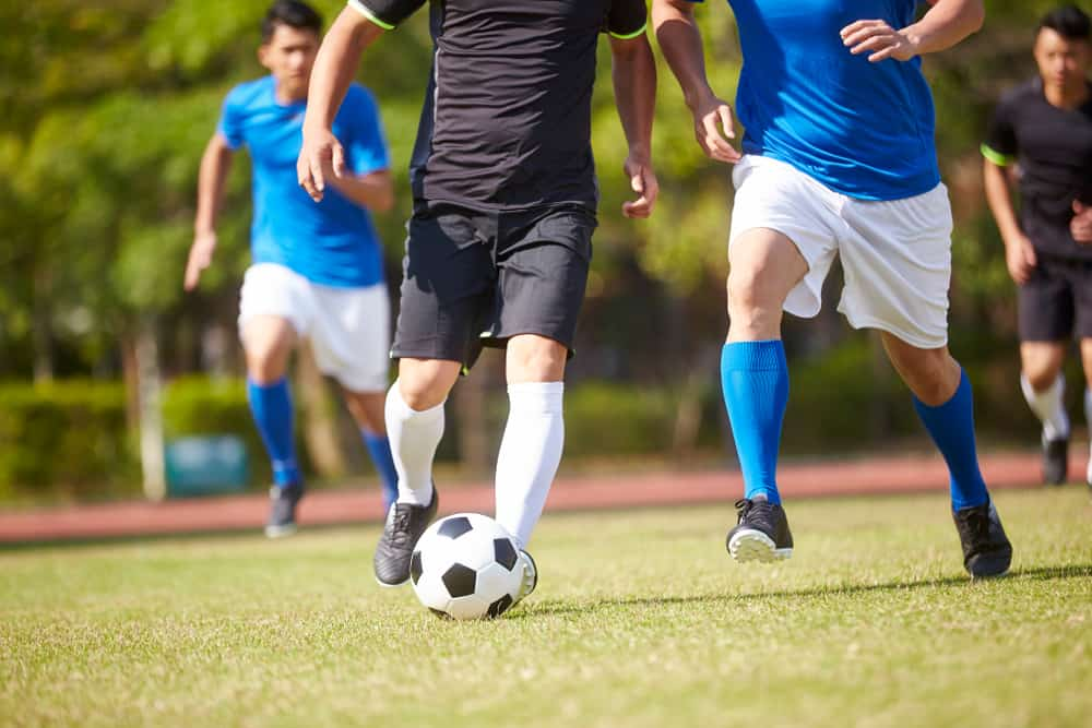 men playing soccer kicking soccer ball sports injuries